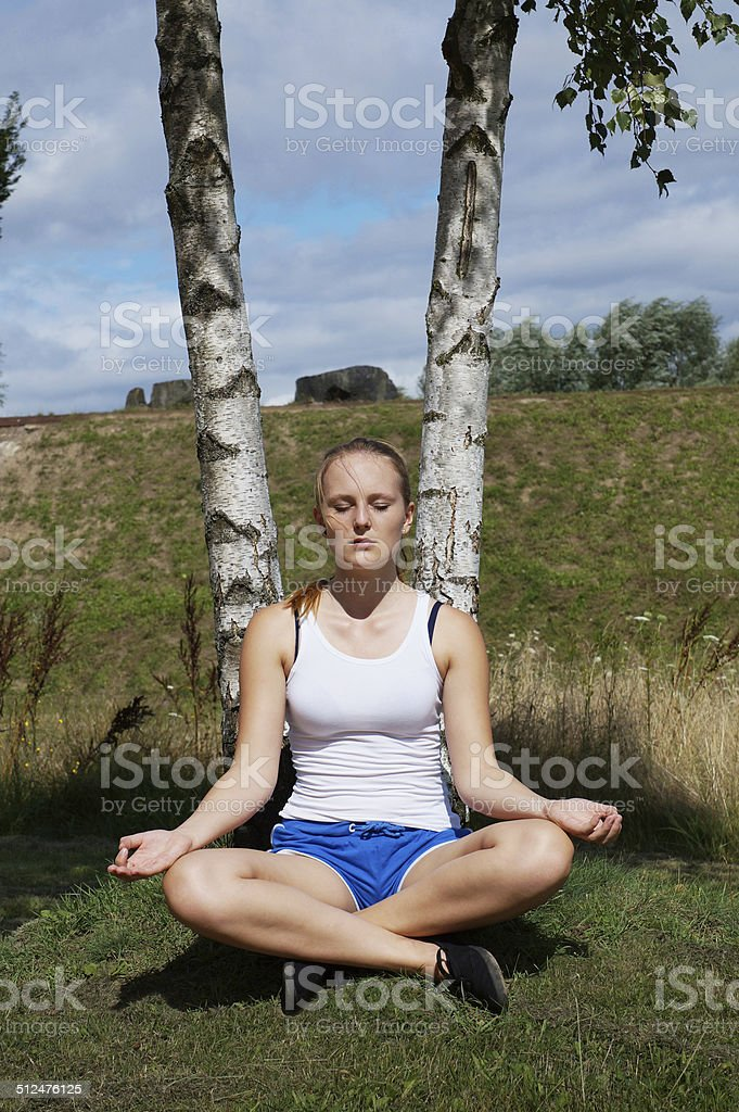 young woman in lotus pose stock photo