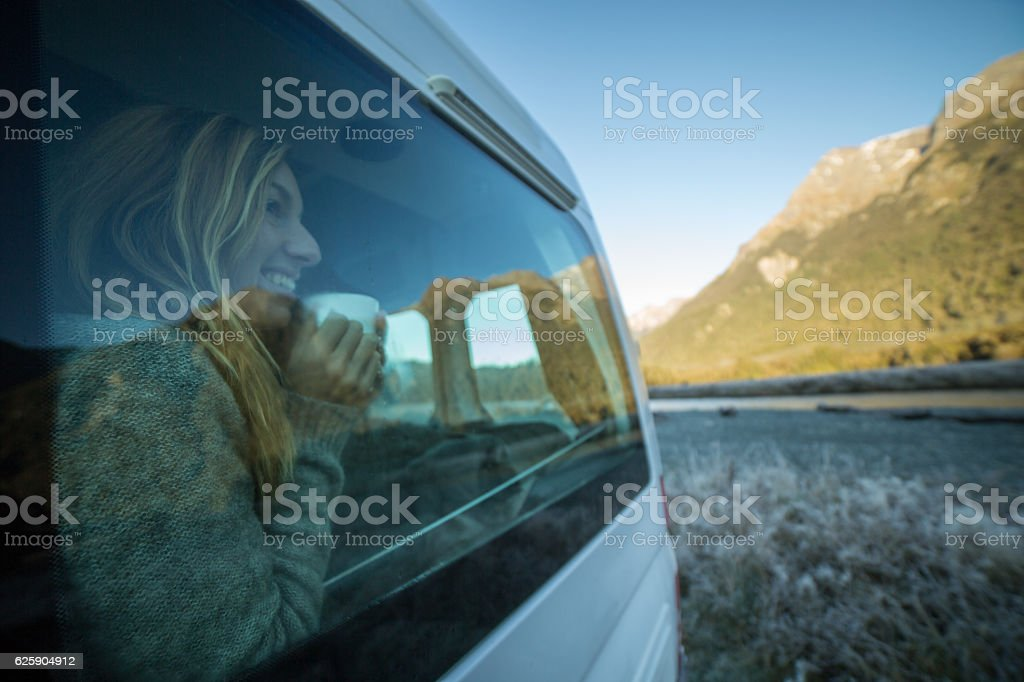 Young woman in motorhome drinks tea and looks through window stock photo