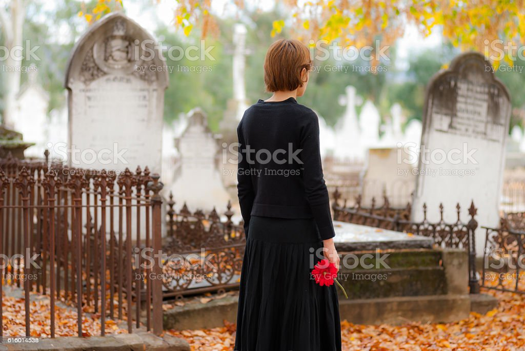 Young woman in mourning walking in cemetery in fall with red flower stock photo