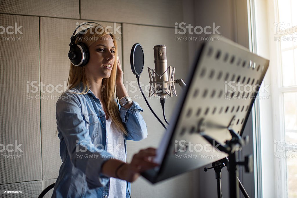Young woman in music studio singing and recording new song. stock photo