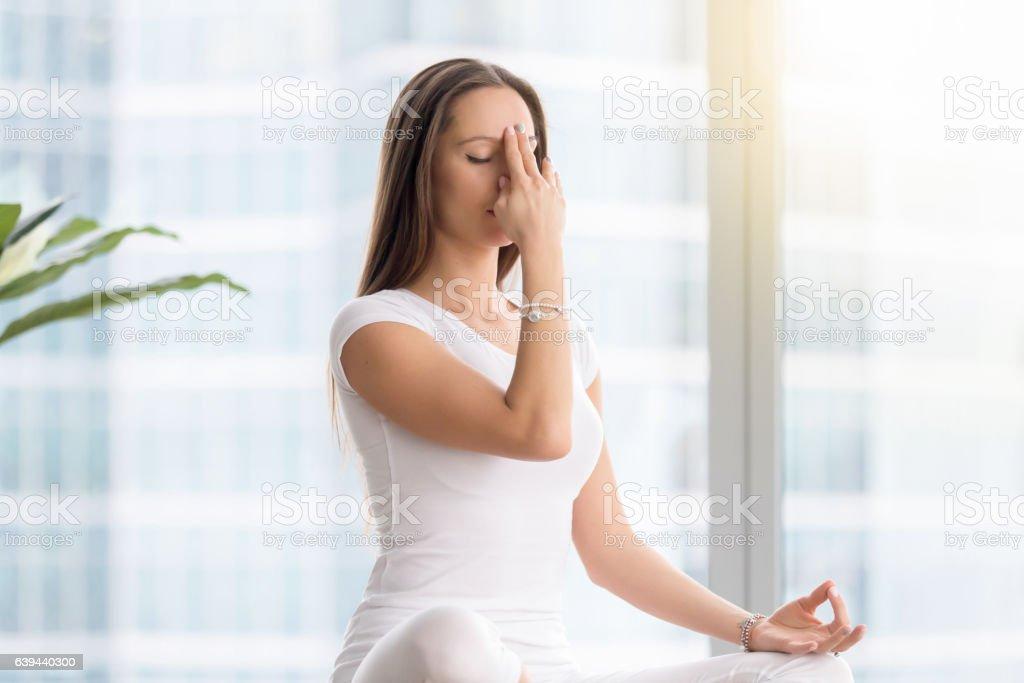 Young woman in nadi shodhana pranayama against floor window stock photo