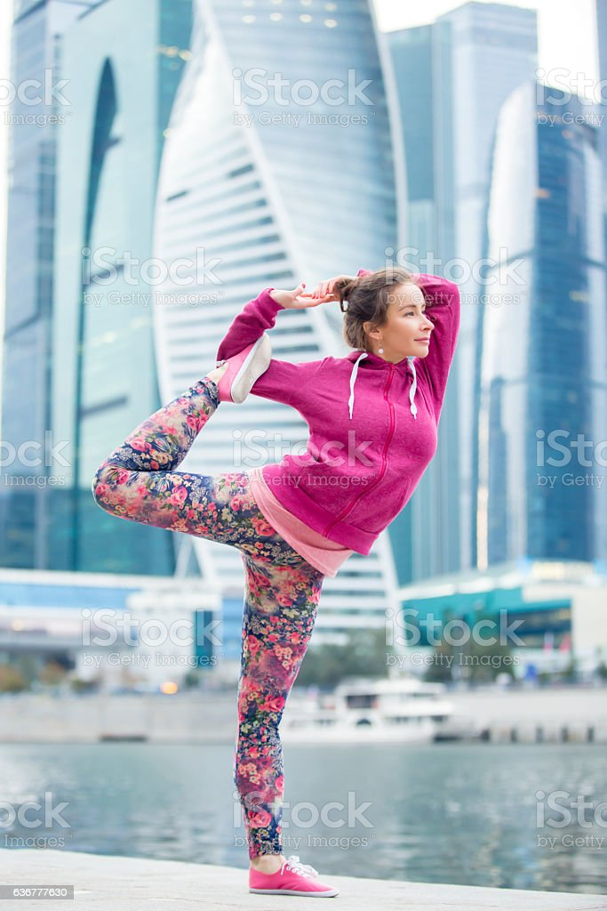 Young woman in Natarajasana pose against the skyscrapers stock photo
