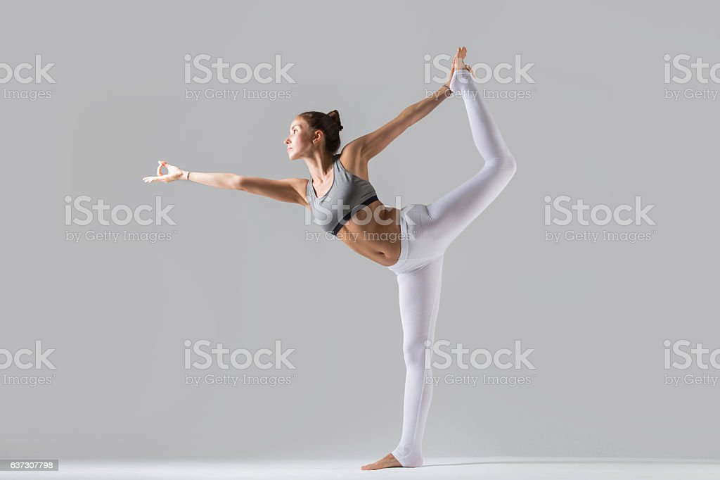 Young woman in Natarajasana pose, grey studio background stock photo