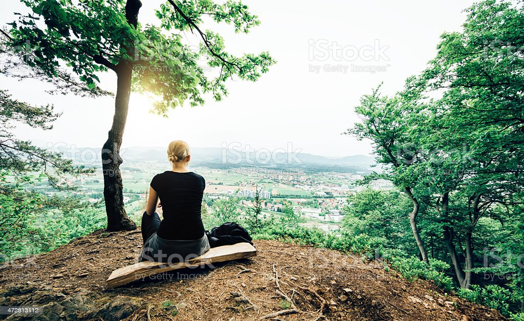 Young Woman In Nature Looking Down On The City stock photo