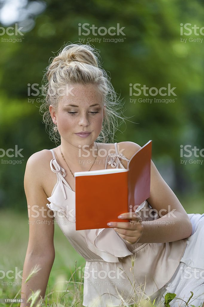 Young woman in nature reading a book. royalty-free stock photo