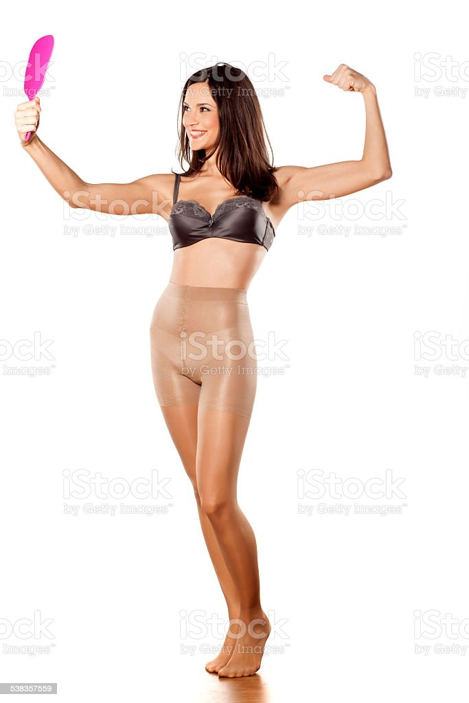 Young woman in nylon stockings and bra on white background stock photo