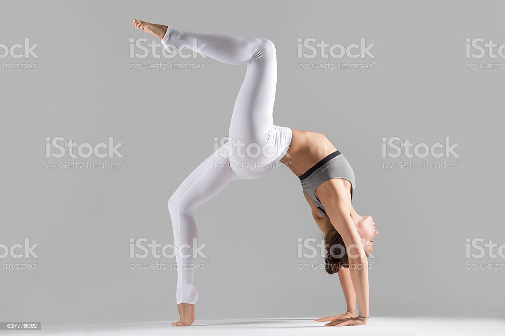 Young woman in One legged Wheel pose, grey studio stock photo