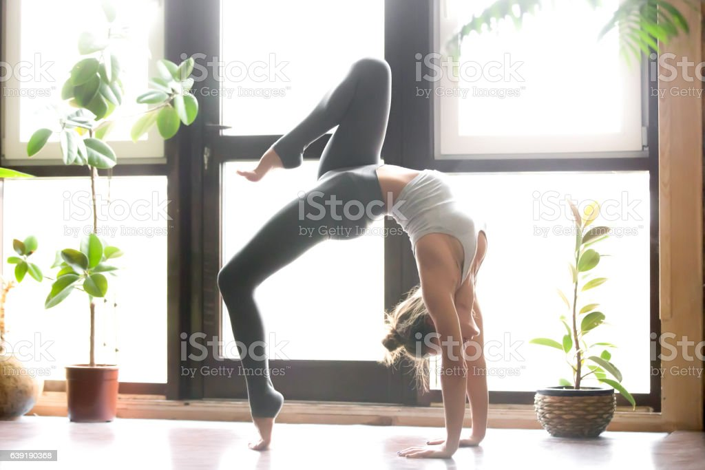 Young woman in One legged Wheel pose, home interior background stock photo