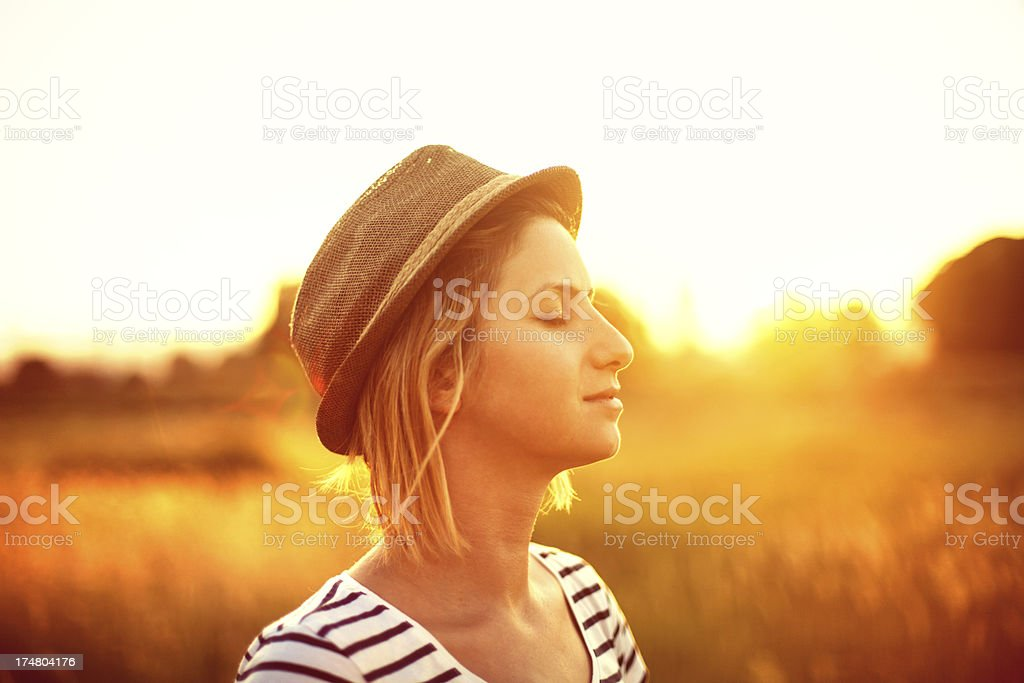 Young woman in open field facing sun royalty-free stock photo