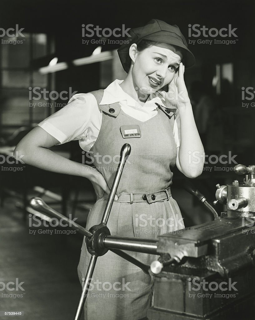Young woman in overalls standing by lathe in factory, (B&W) royalty-free stock photo