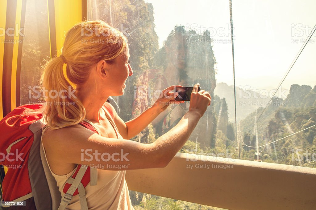 Young woman in overhead cable car taking smart phone picture stock photo