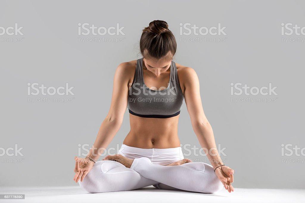 Young woman in Padmasana pose, grey studio background stock photo