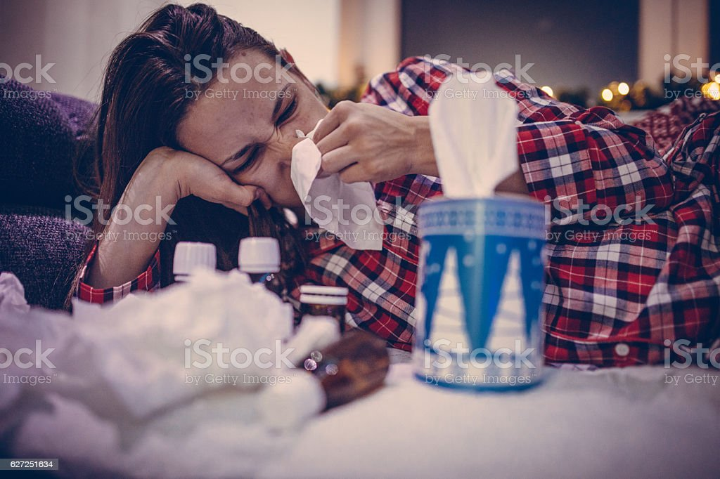 Young woman in pajamas blowing nose stock photo