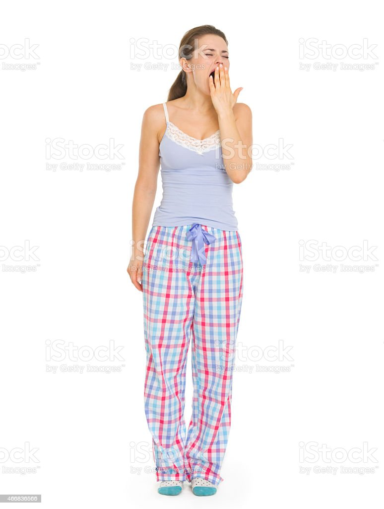 young woman in pajamas yawing stock photo
