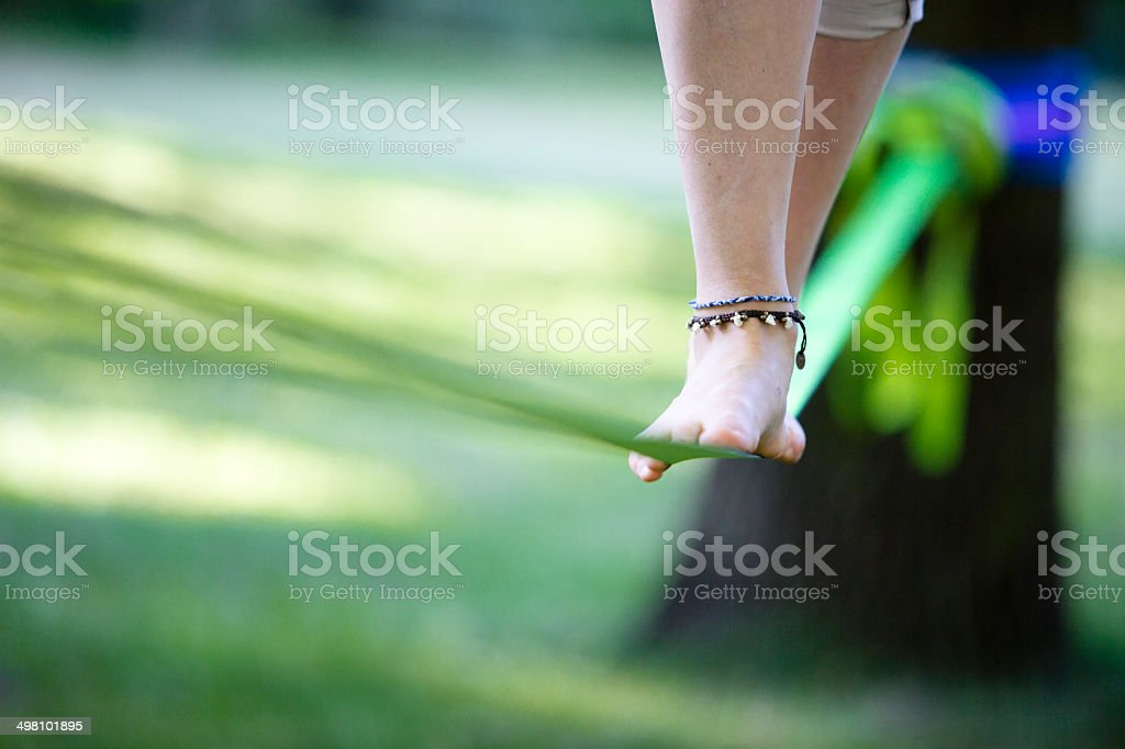 young woman in park balancing on a slackline royalty-free stock photo