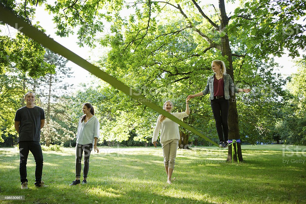 young woman in park balancing on a slackline stock photo