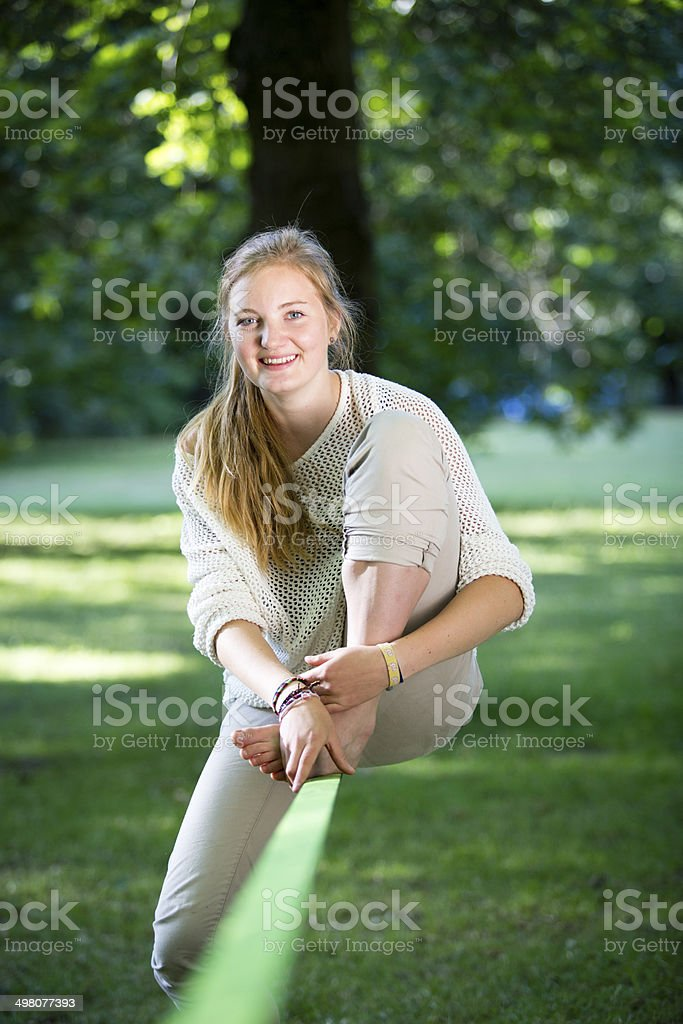 young woman in park sitting on a slackline stock photo