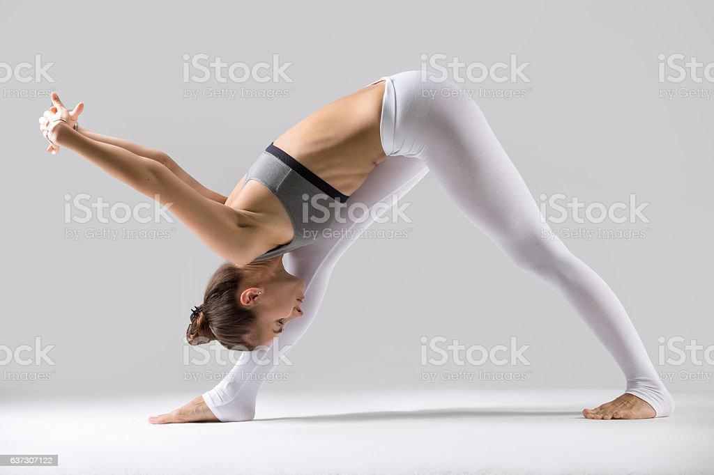 Young woman in Parsvottanasana pose, grey studio background stock photo