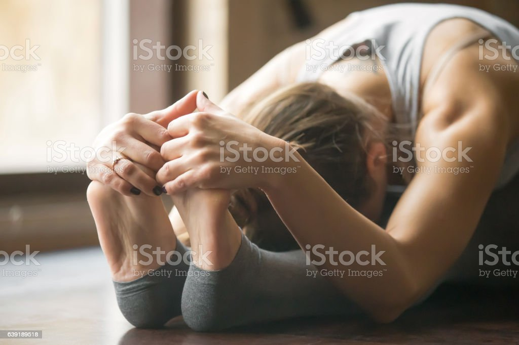 Young woman in paschimottanasana pose, home interior background, stock photo
