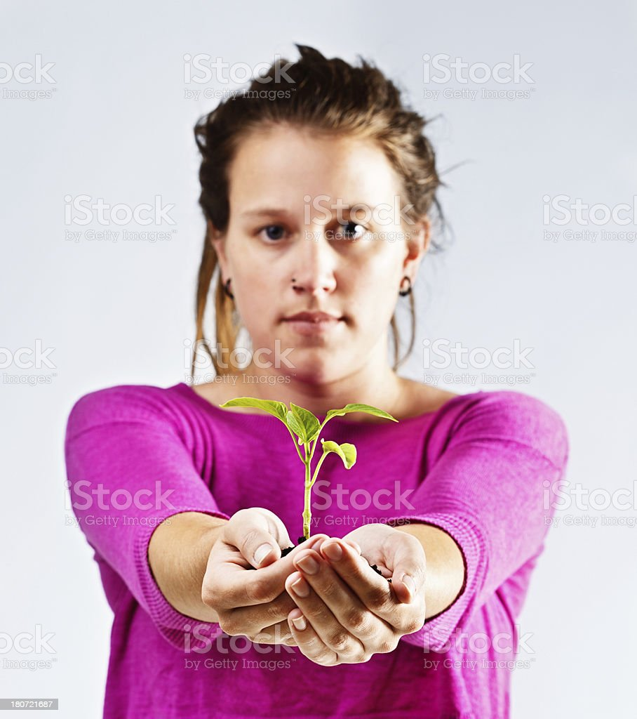 Young woman in pink holds out growing seedling, looking serious royalty-free stock photo