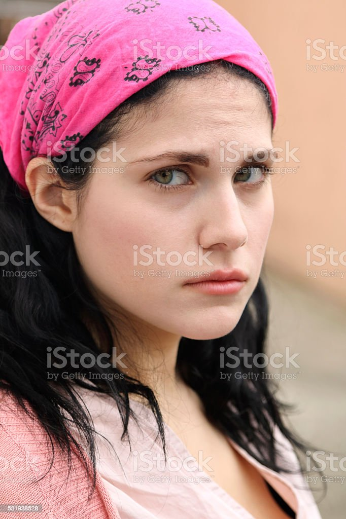 Young woman in pink kerchief with sad eyes stock photo