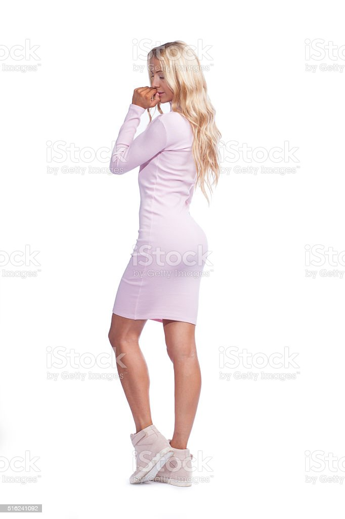 young woman in pink skin-tight dress isolated stock photo