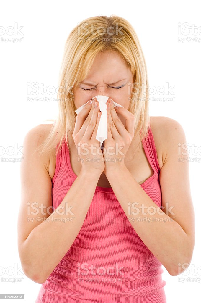 Young woman in pink top sneezing royalty-free stock photo