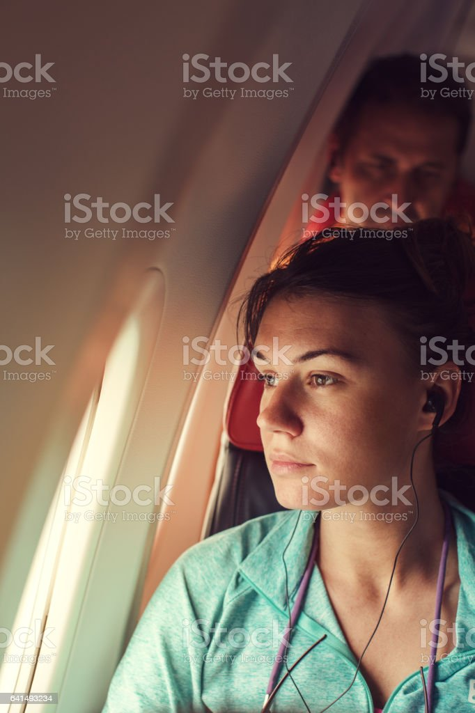 Young woman in plane sitting by the window stock photo