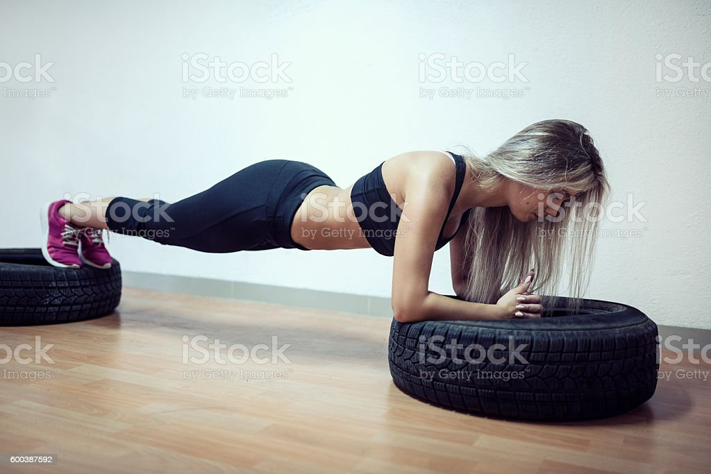Young Woman in Plank Position on Tires at Gym stock photo