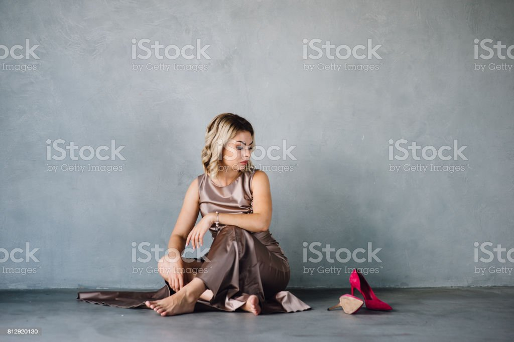 young woman in purple dress sitting on a floor stock photo