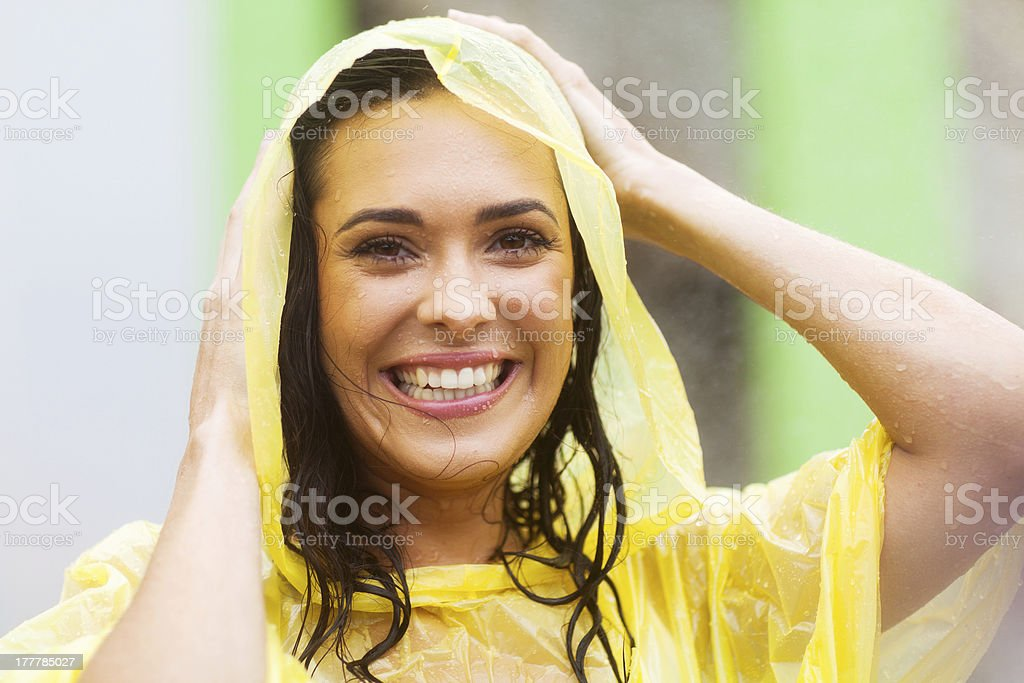 young woman in raincoat outdoors stock photo