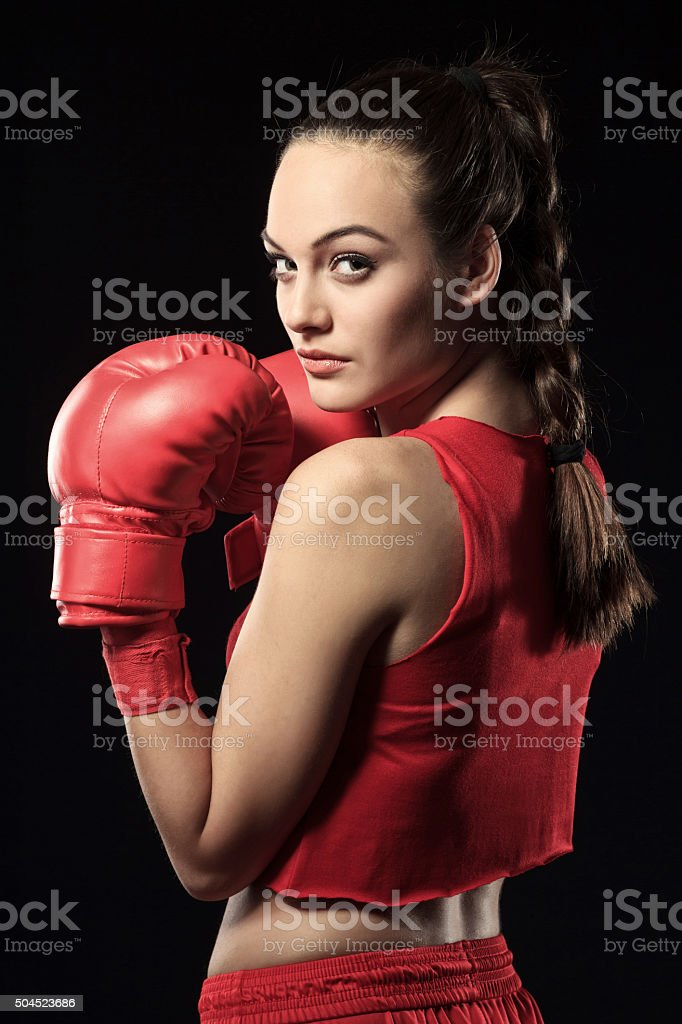 Young Woman in Red Boxing Outfit looking over shoulder-portrait stock photo