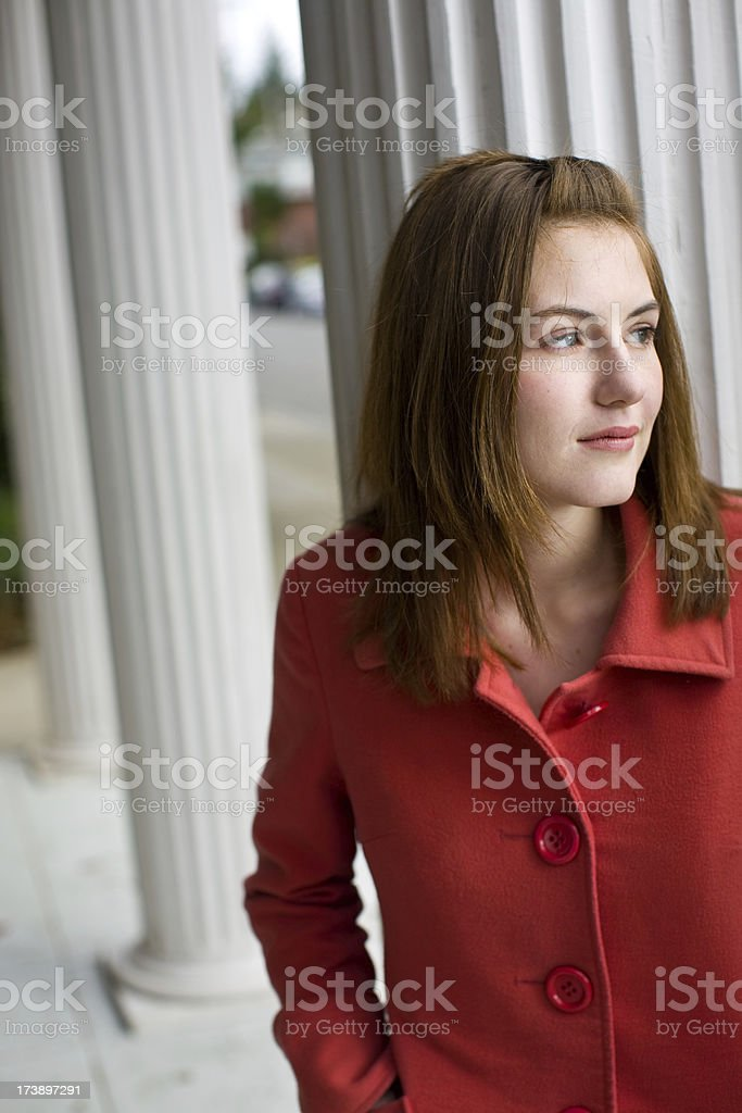 young woman in red coat looking to the side royalty-free stock photo