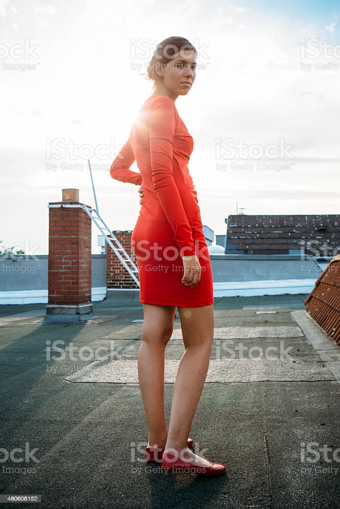 young woman in red dress and with backlit on rooftop stock photo