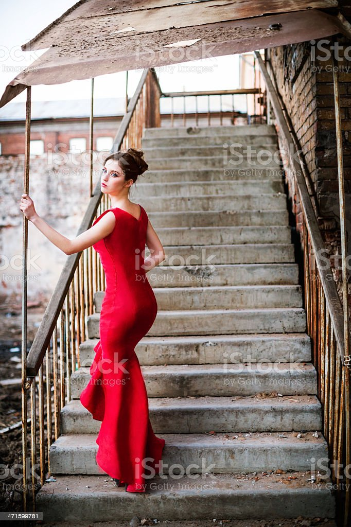 Young woman in red dress at old staircase royalty-free stock photo
