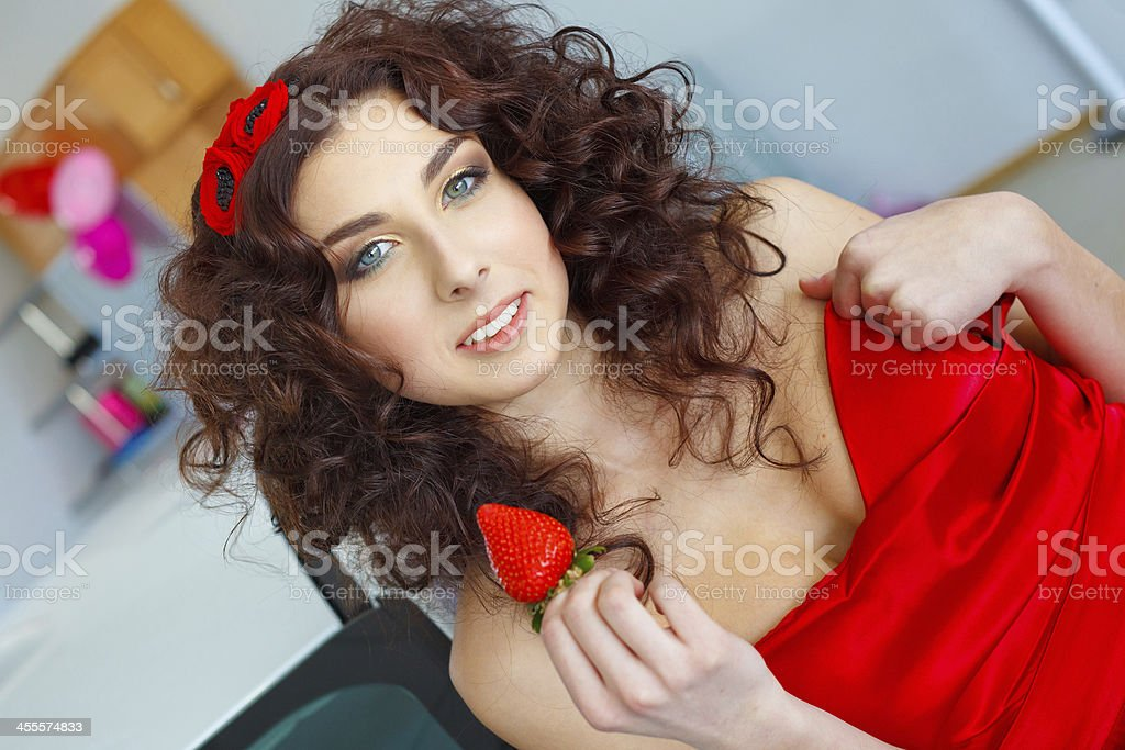 Young woman in red dress holding strawberry leaning on car royalty-free stock photo