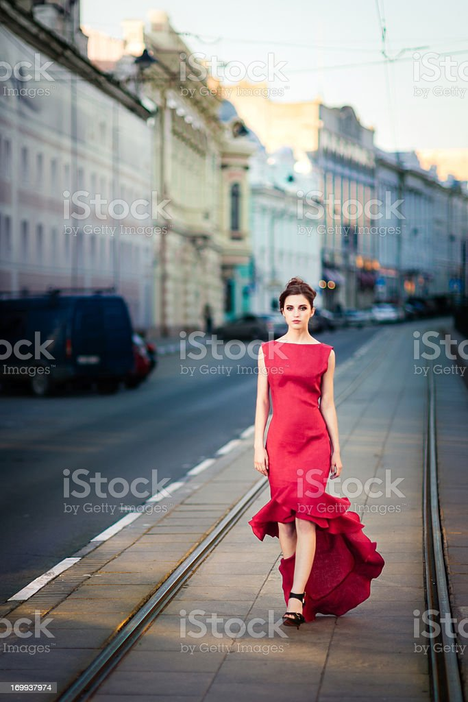 Young woman in red dress on city streets stock photo