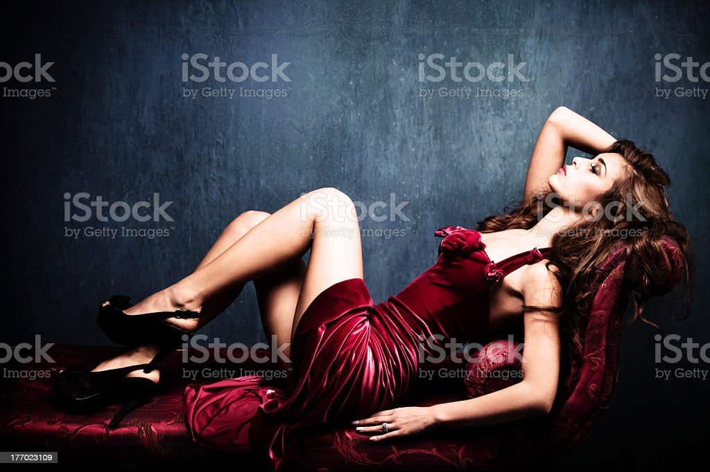 Young woman in red dress rests on a chair stock photo