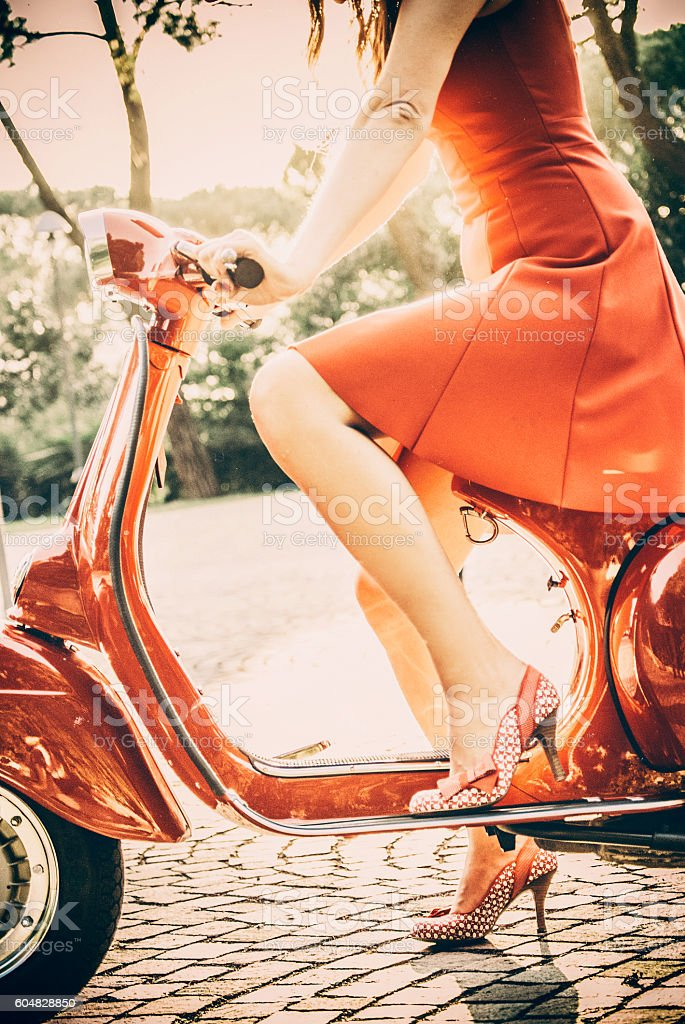 Young Woman In Red Dress Riding a Vintage Scooter stock photo