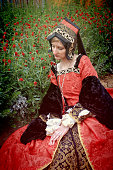 Young Woman in Red Renaissance Dress Sitting Beside Flower Garden