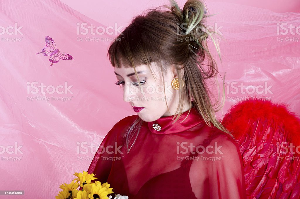 Young woman in red wings looking down at flowers royalty-free stock photo
