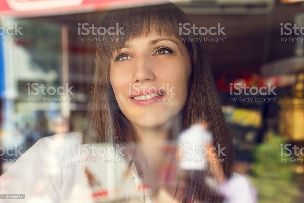 Young woman in restaurant. Beauty adult girl looking through window stock photo