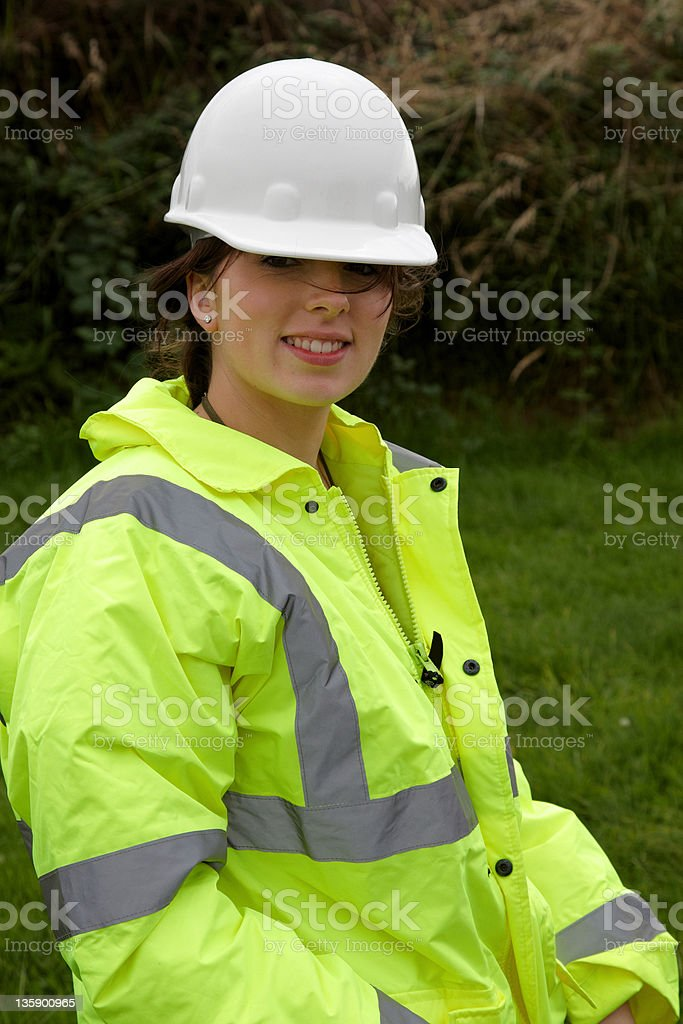 Young woman in safety jacket and helmet stock photo