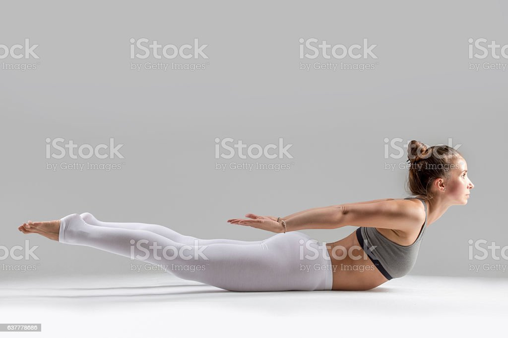 Young woman in Salabhasana pose, grey studio background stock photo