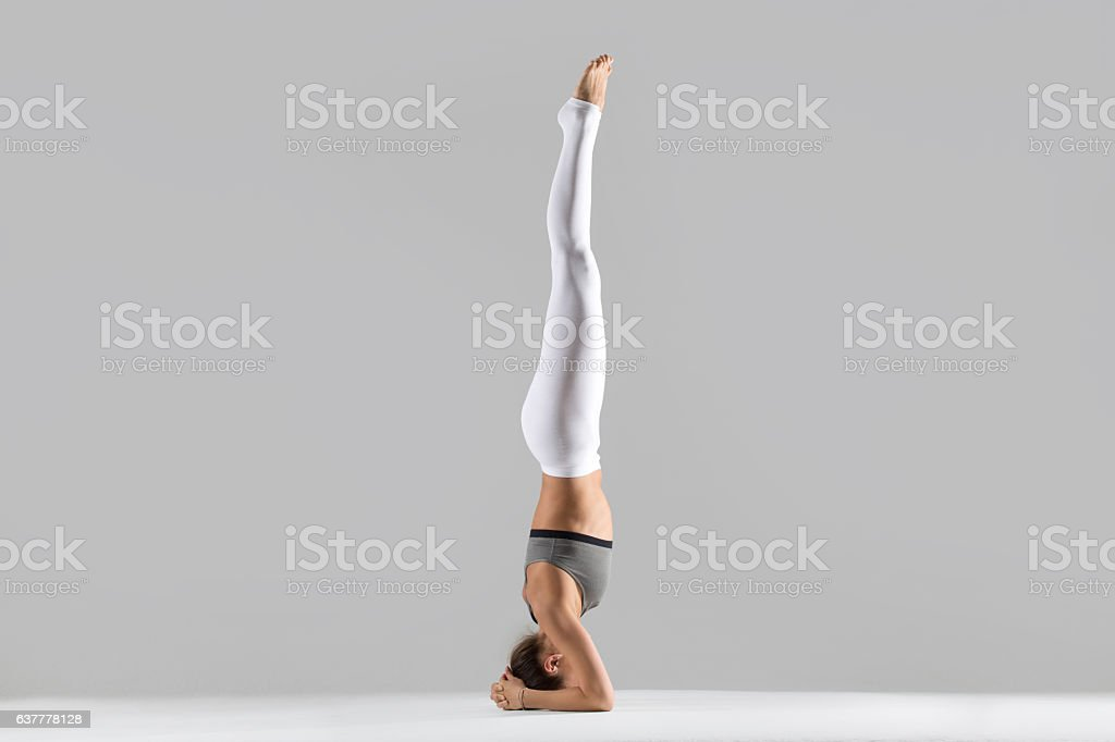 Young woman in salamba sirsasana pose, grey studio background stock photo