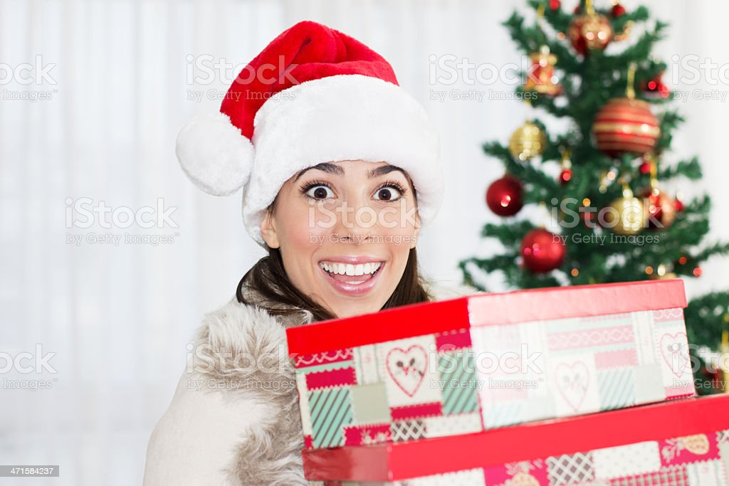 Young Woman in Santa hat holding  her Christmas gifts. royalty-free stock photo