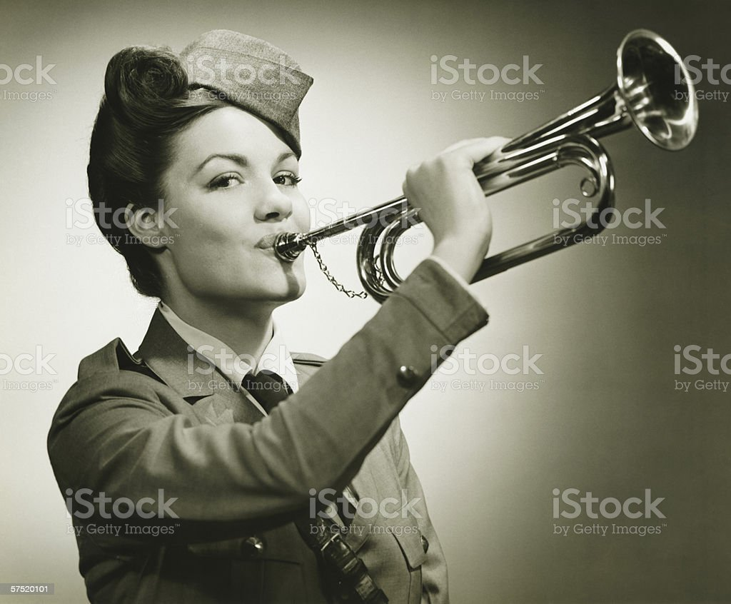Young woman in soldiers uniform playing on trumpet, (B&W), portrait stock photo