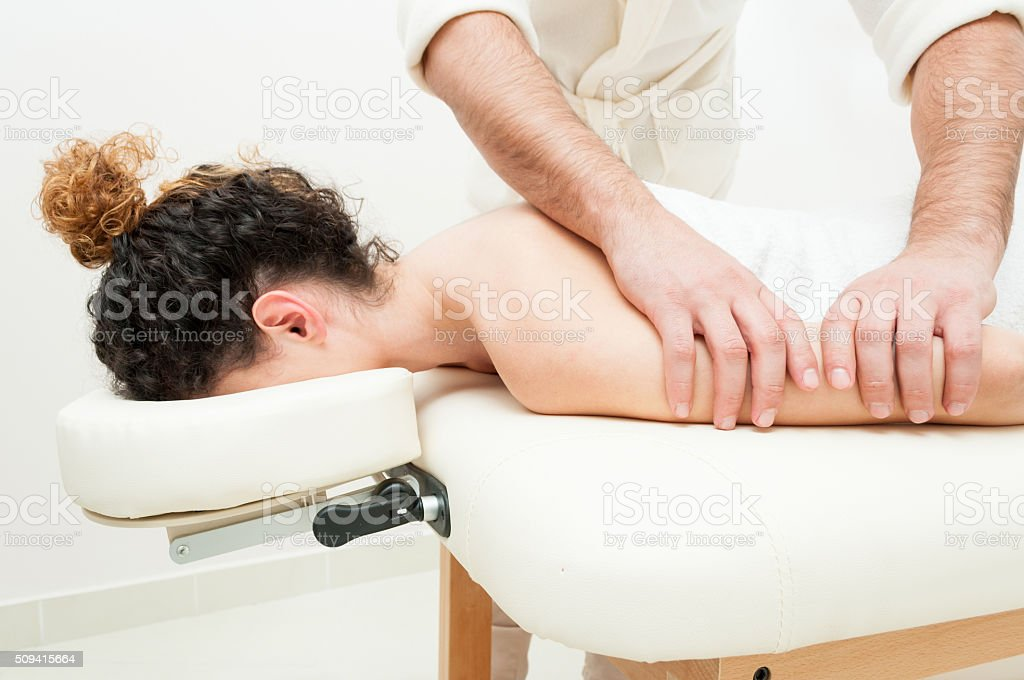 Young woman in spa getting a  body relaxing massage stock photo