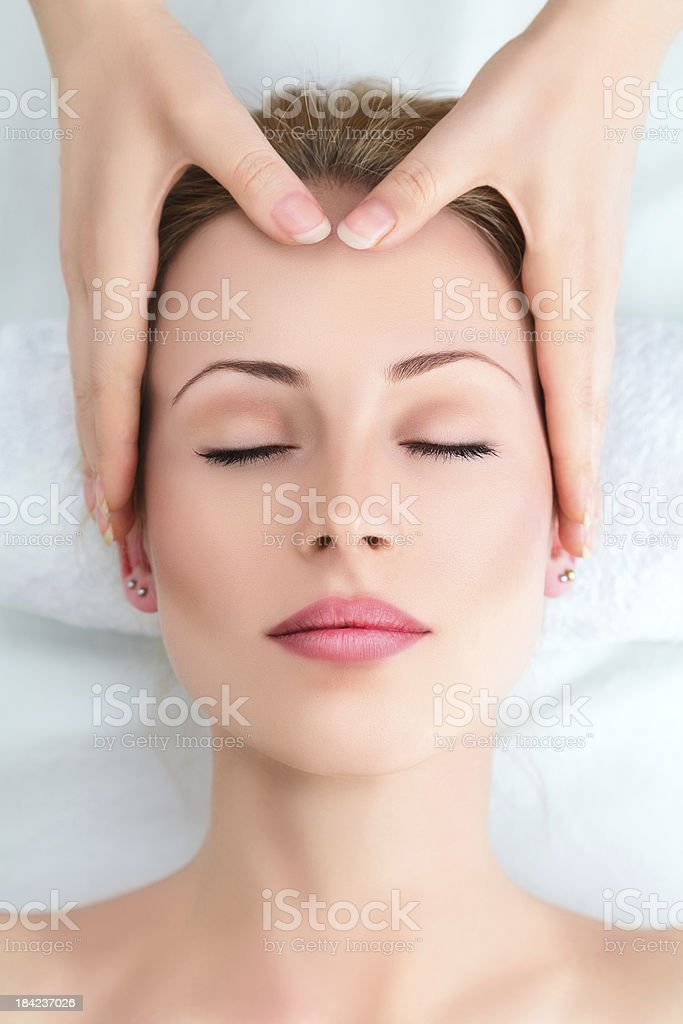 Young woman in spa getting forehead massage stock photo