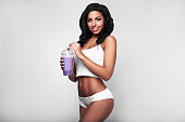Young woman in sports gym wear with fruit fresh drink